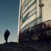 a distant shot of Fred walking away outside the industrial buildings where he and Philip talk about the stealth paint