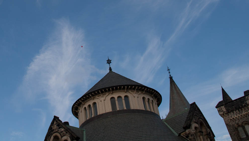 turreted tower with red balloon and blue blue skies