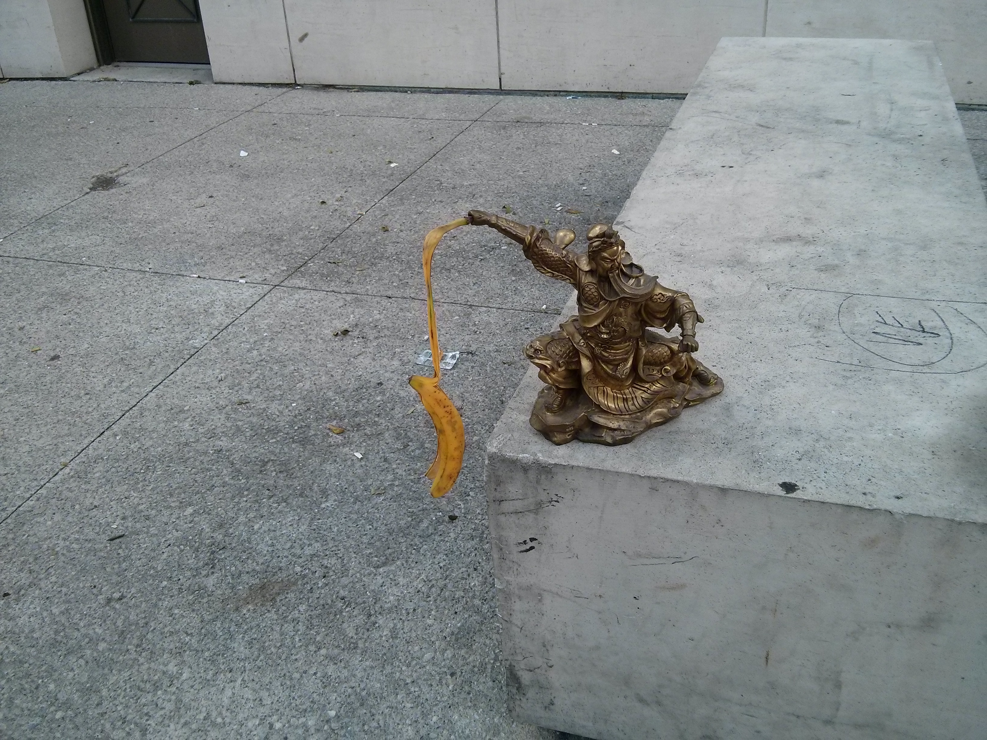 statue with a banana peel stuck into his hand