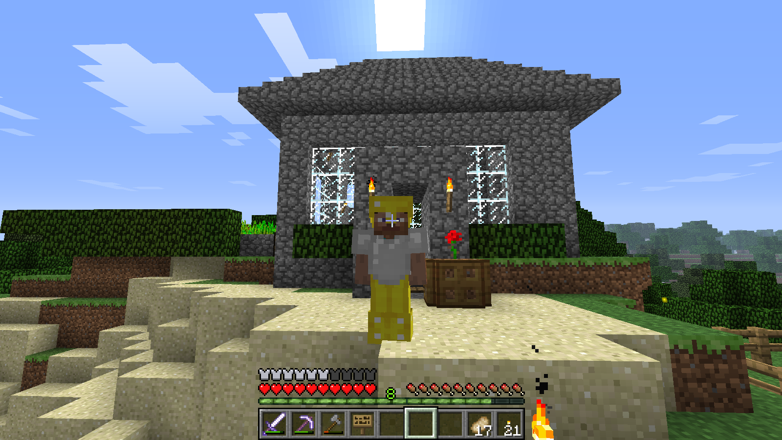 minecraft figure standing in front of a blocky stone house with a triangle roof, wearing silver and gold armour