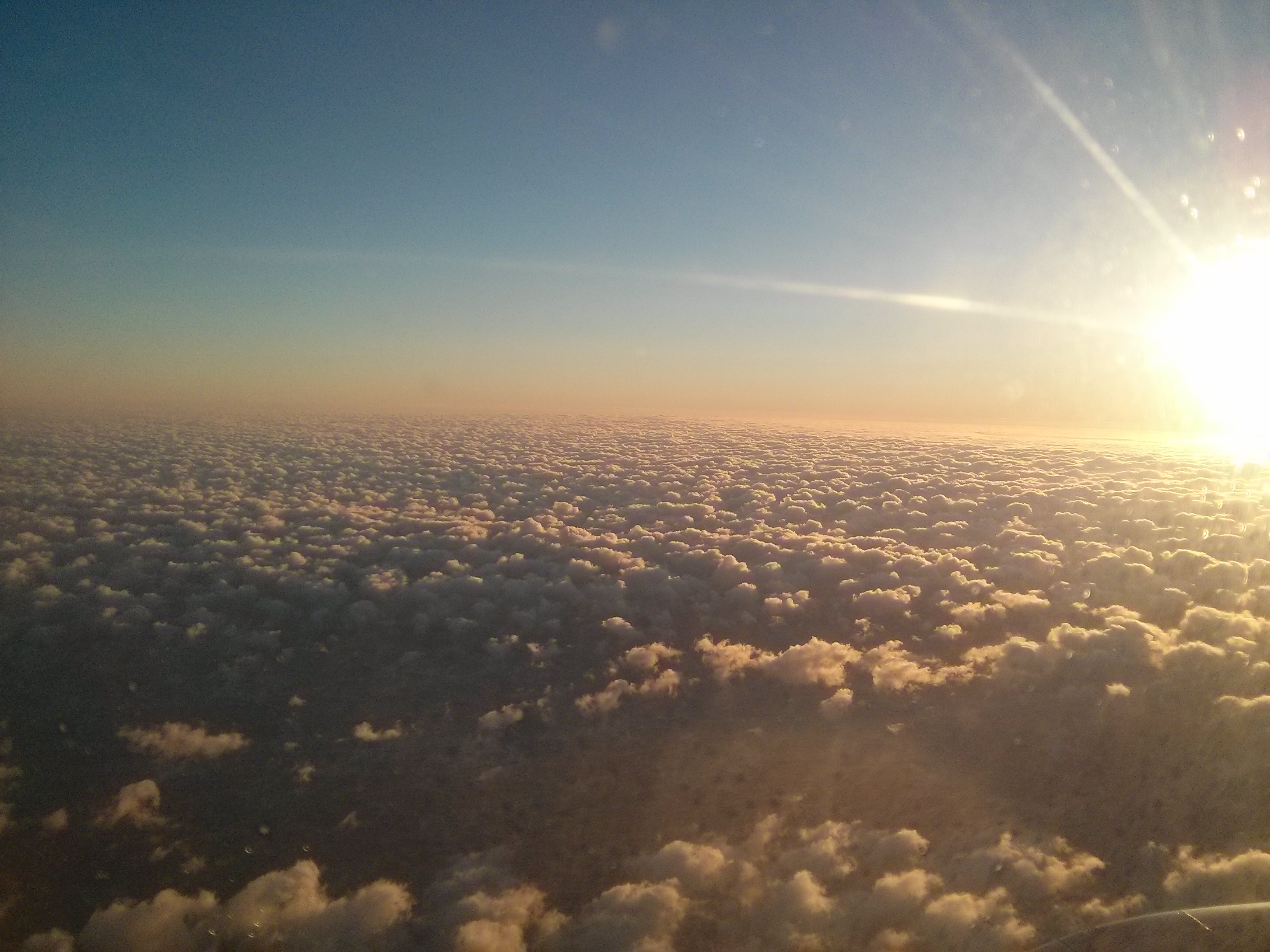 fluffy clouds with sun rising on the right side, blue sky gradient into white-pink tinted clouds