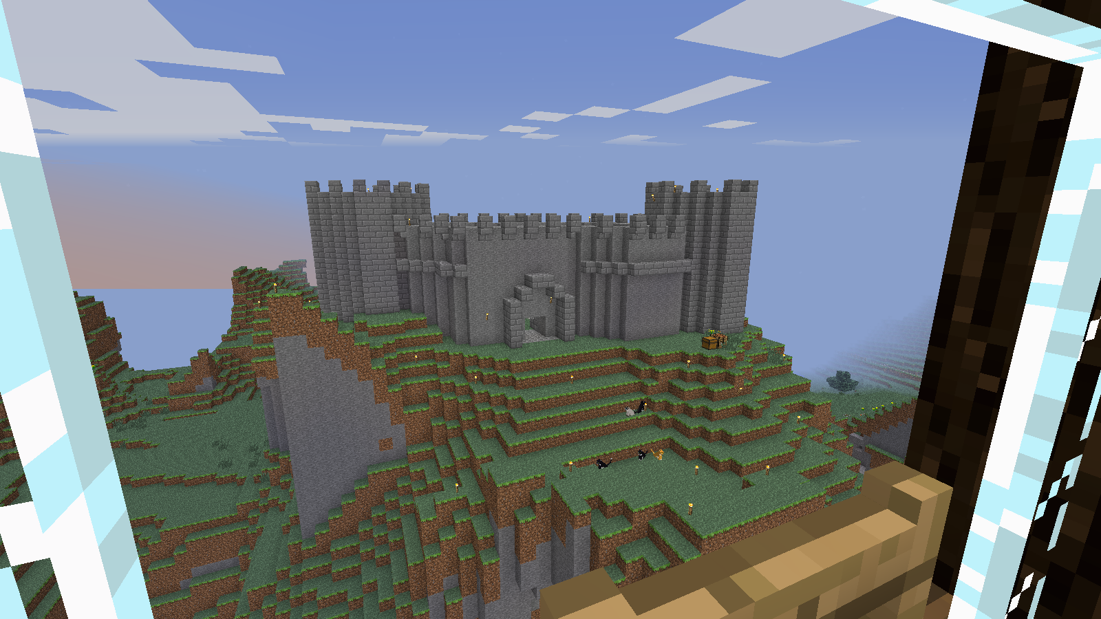 screencap of grey-stone castle with two towers of cobblestone and linking walls with stone
