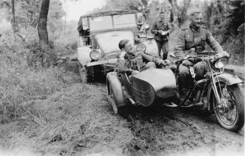 Немецкие солдаты на трофейном советском мотоцикле ТИЗ АМ-600 на лесной дороге. На втором плане  немецкий грузовик Крупп Протце Krupp Protze