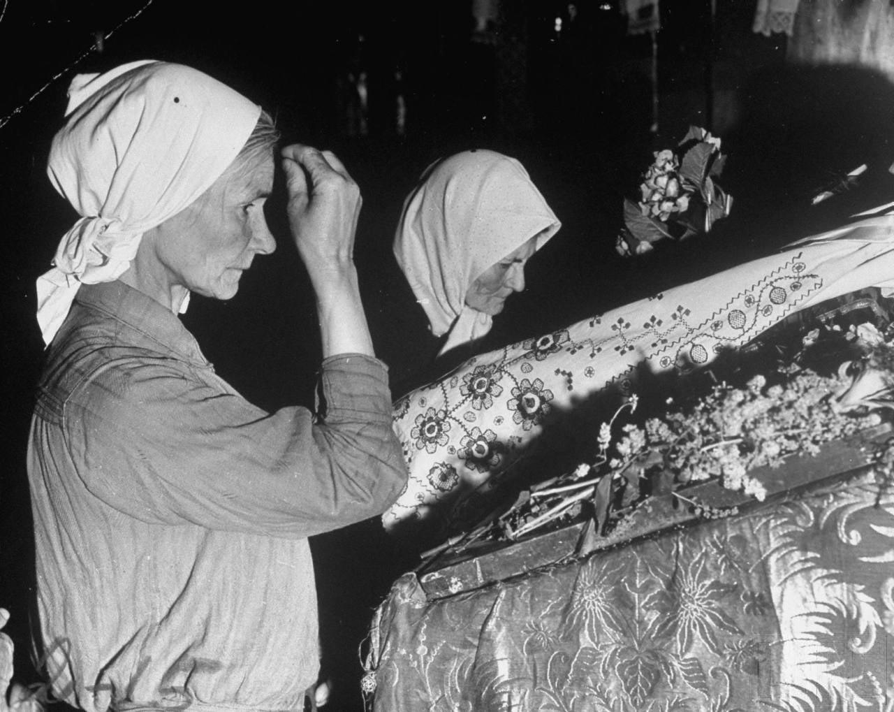 77Женщины молятся перед иконой Святого Петра и Павла в католическом соборе.