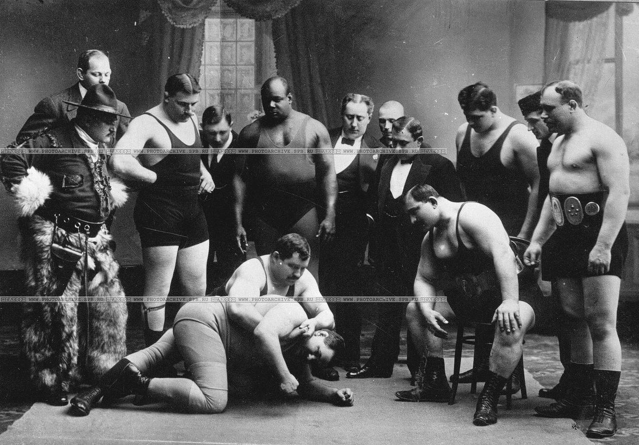 0_a6a0a_aa91fe9e_XXXLГруппа участников чемпионата наблюдает за схваткой двух борцов
