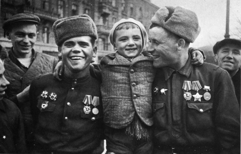Советские солдаты с ребенком в освобожденной Одессе. Фотография продолжает эпизод встречи жителями Одессы бойцов, освободивших город.