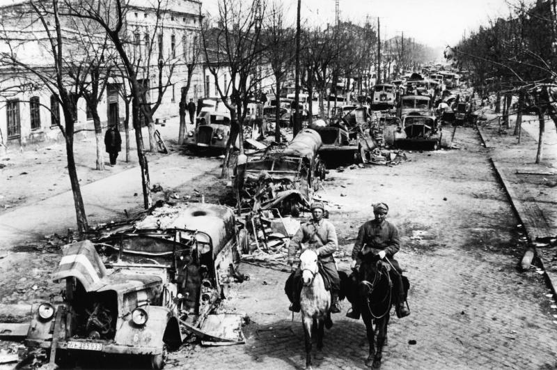 Советские солдаты едут по улице освобожденной Одессы, забитой брошенной немцами техникой.