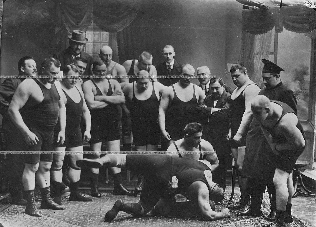 Группа участников чемпионата наблюдает за борьбой двух борцов (первый в первом ряду слева стоит И.М.Поддубный