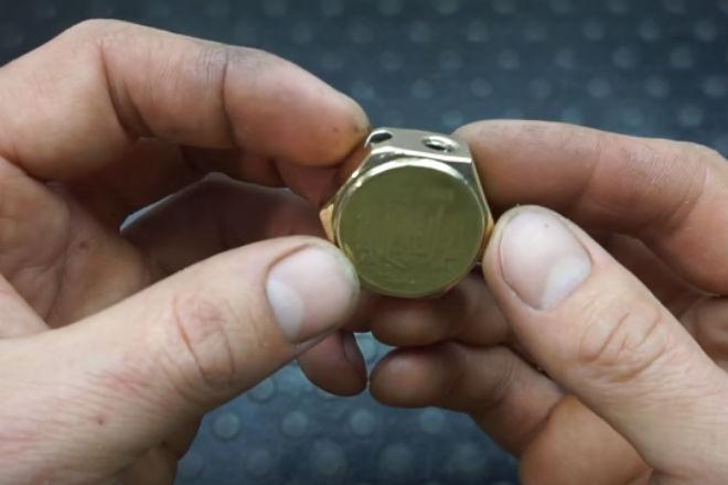 Две монеты крепятся по сторонам гайки в качестве стенок
