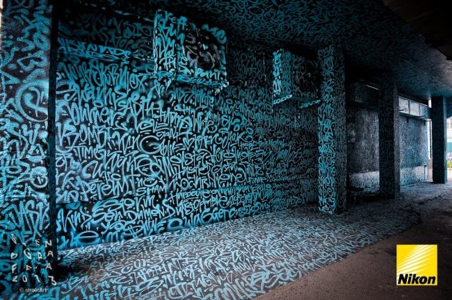 льтрафиолете стена, покрытая каллиграфическими тегами, светится надписью «Все ваши стены принадлежат нам».