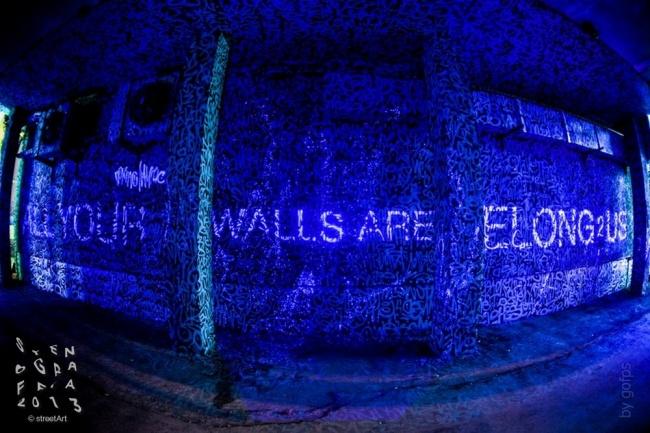 льтрафиолете стена, покрытая каллиграфическими тегами, светится надписью «Все ваши стены принадлежат нам».2