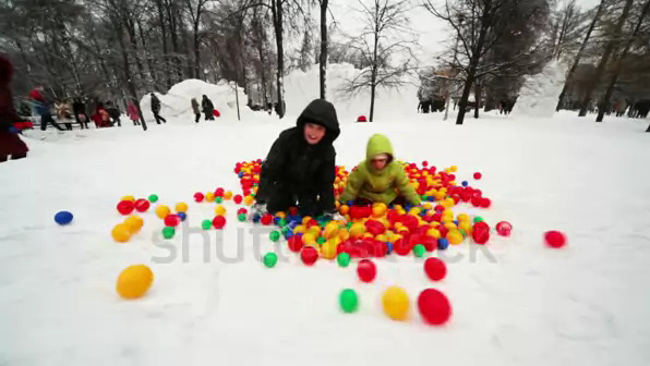 stock-footage-boy-and-little-girl-play-in-pile-of-colored-balls-in-park-at-winter-day