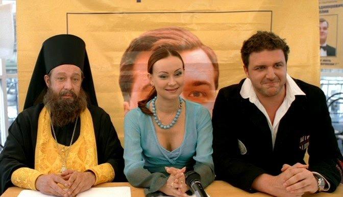 Отец Инокентий, Нона и Максим ведут передачу о новом кандидате. Кадр из фильма «День выборов»