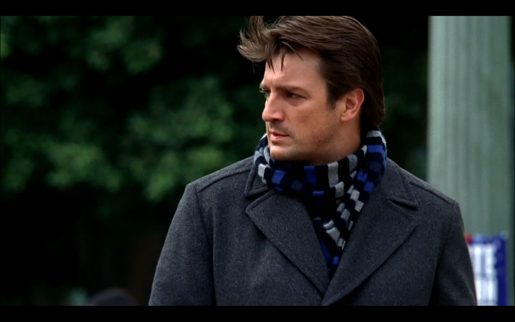 Richard Castle with blue striped scarf looking left