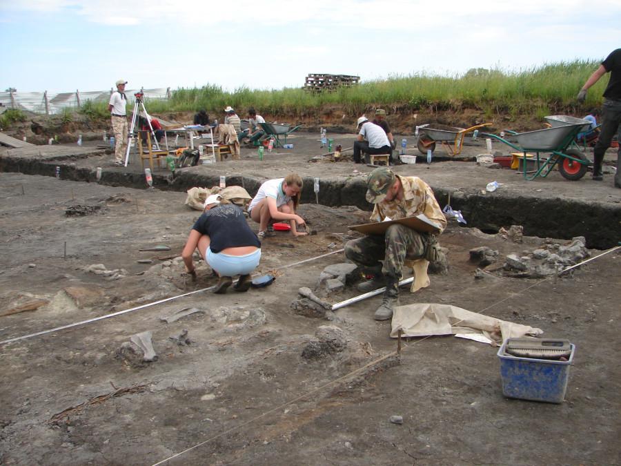 Девушки расчищают деревянный настил и  развал камней.