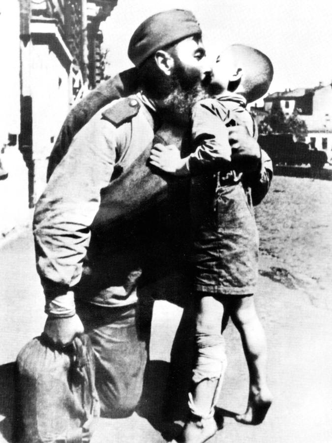 Вернувшийся с фронта солдат целует своего сына.