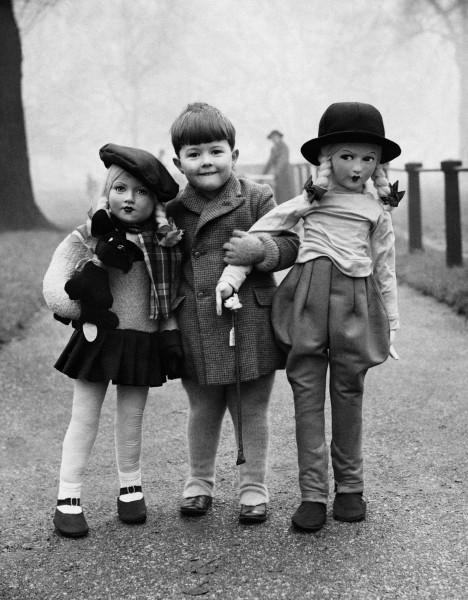 Boy with two large dolls, c. 1950's, by Elliott Erwitt