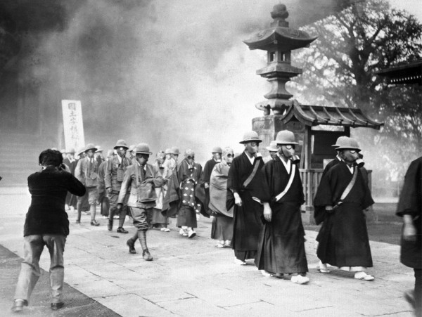 Buddhist priests of the Big Asakusa Temple prepare for the Second Sino-Japanese War by wearing gas masks during training for future aerial attacks [Tokyo, Japan, May 30, 1936]