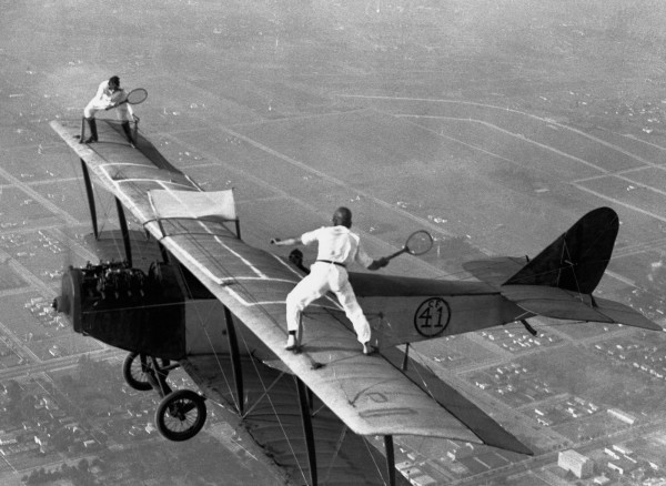 Daredevils in America demonstrating the auto-pilot feature on their biplane by playing tennis on the wings, while in mid-flight, c. 1925