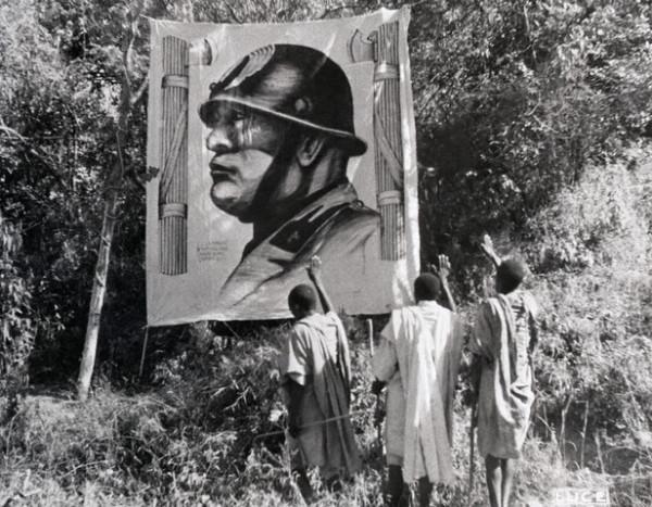 Ethiopians admiring a poster of Benito Mussolini, 1935