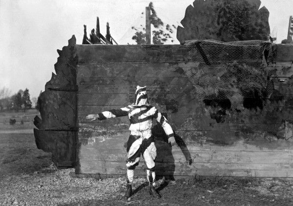 Soldier testing black and white camouflage meant to conceal him while climbing trees, at American University, 1917