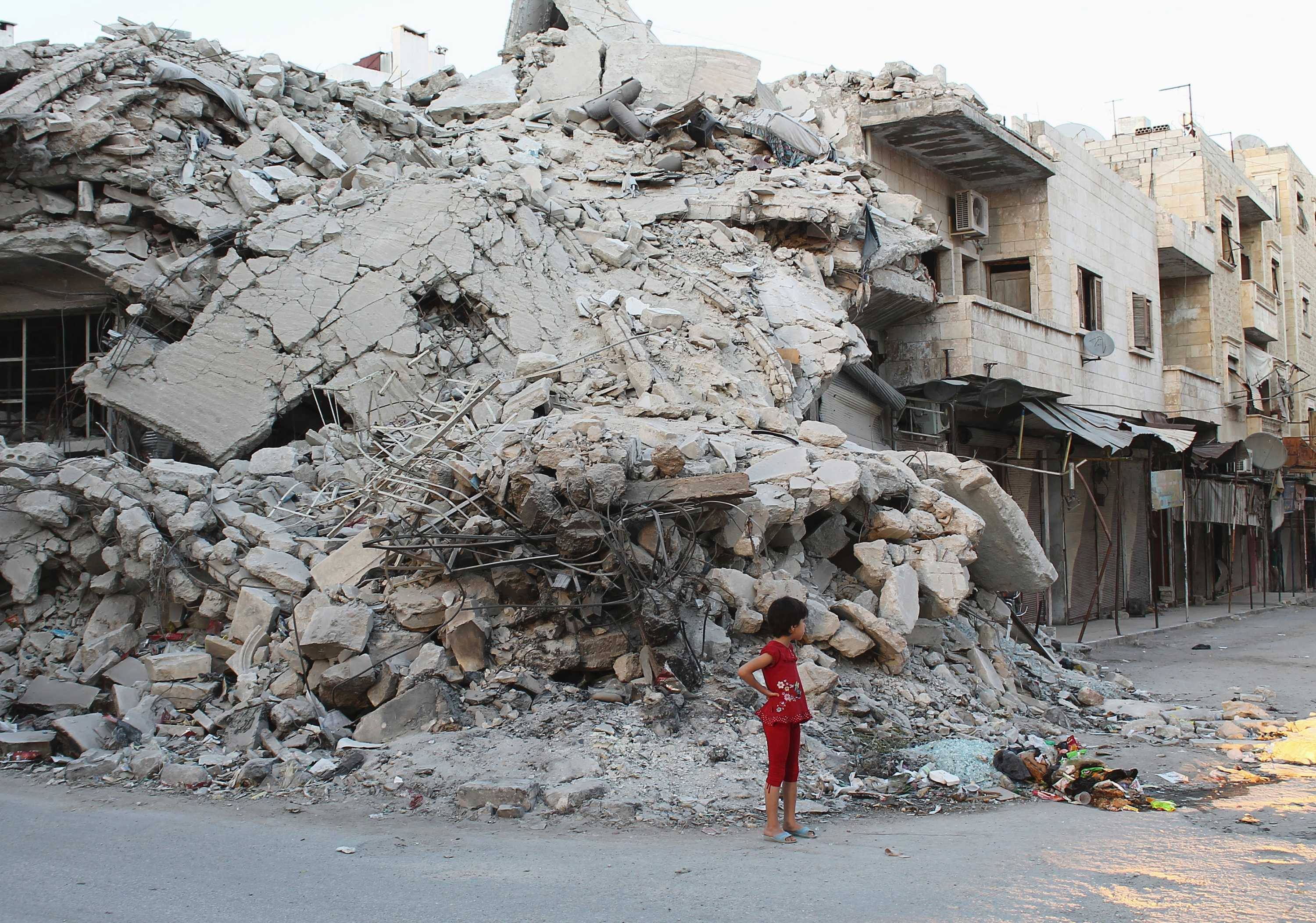 girl-stands-by-building-damaged-by-syrian-forces-data