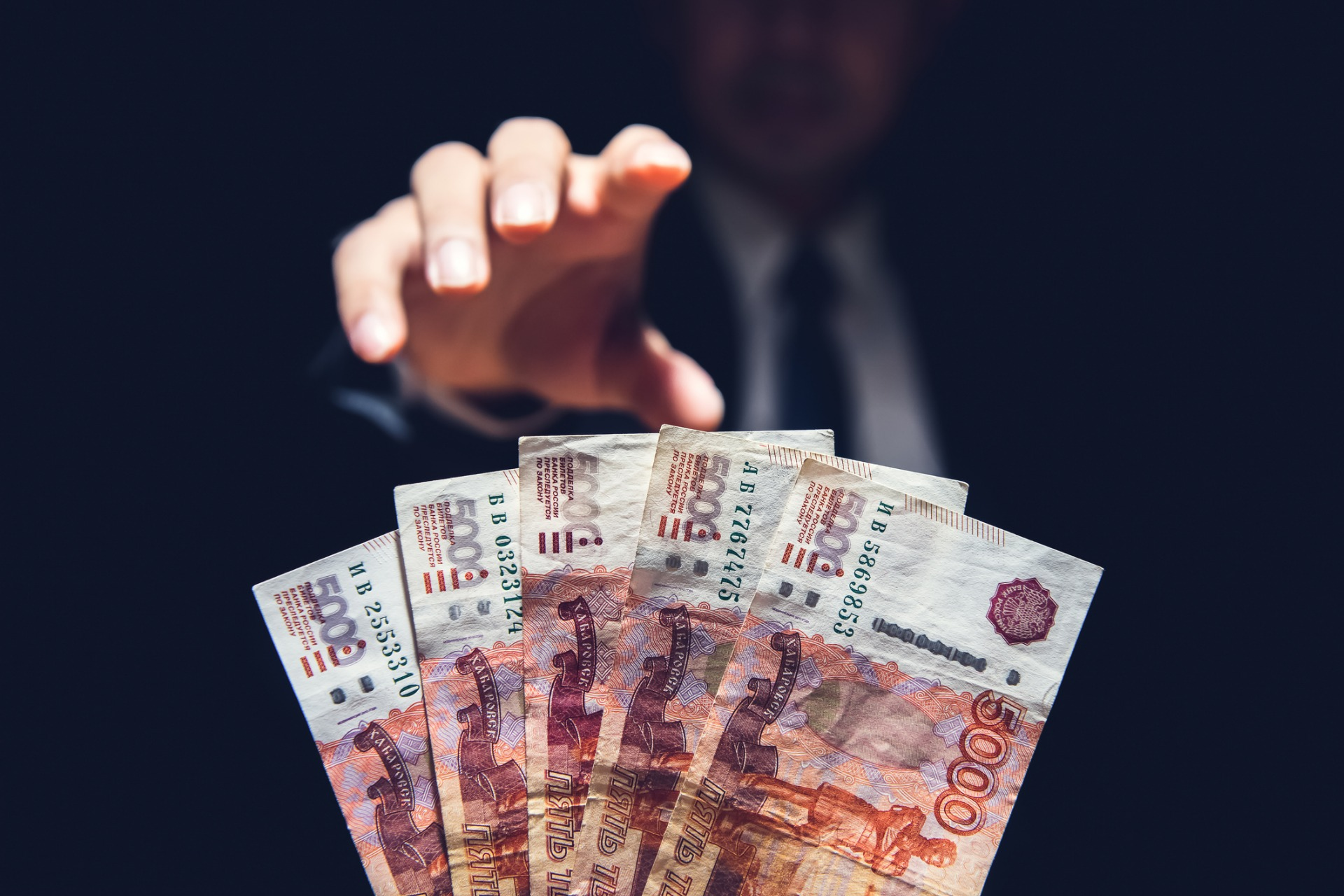 anonymous-businessman-reaching-out-hand-to-grab-money-russian-ruble-picture-id987130422