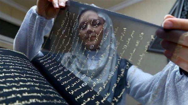 Переписанный Коран золотом по прозрачному черному шелку.