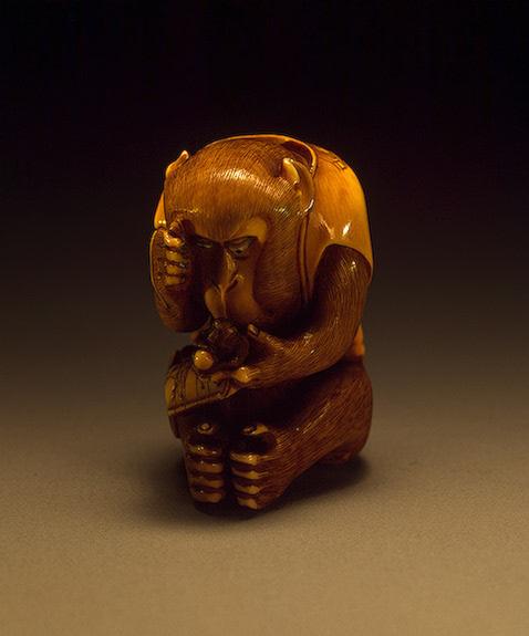 Обезьяна, разглядывающая нэцкэ в виде обезьяны с персиком