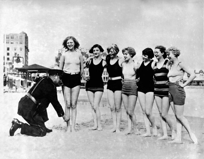 Полицейский измеряет купальники женщин на пляже