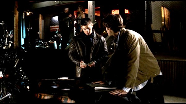 Sam and Dean looking at paper