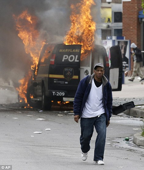 2812E6D700000578-3057819-A_man_walks_past_a_burning_police_vehicle_during_unrest_in_Balti-m-223_1430171775411