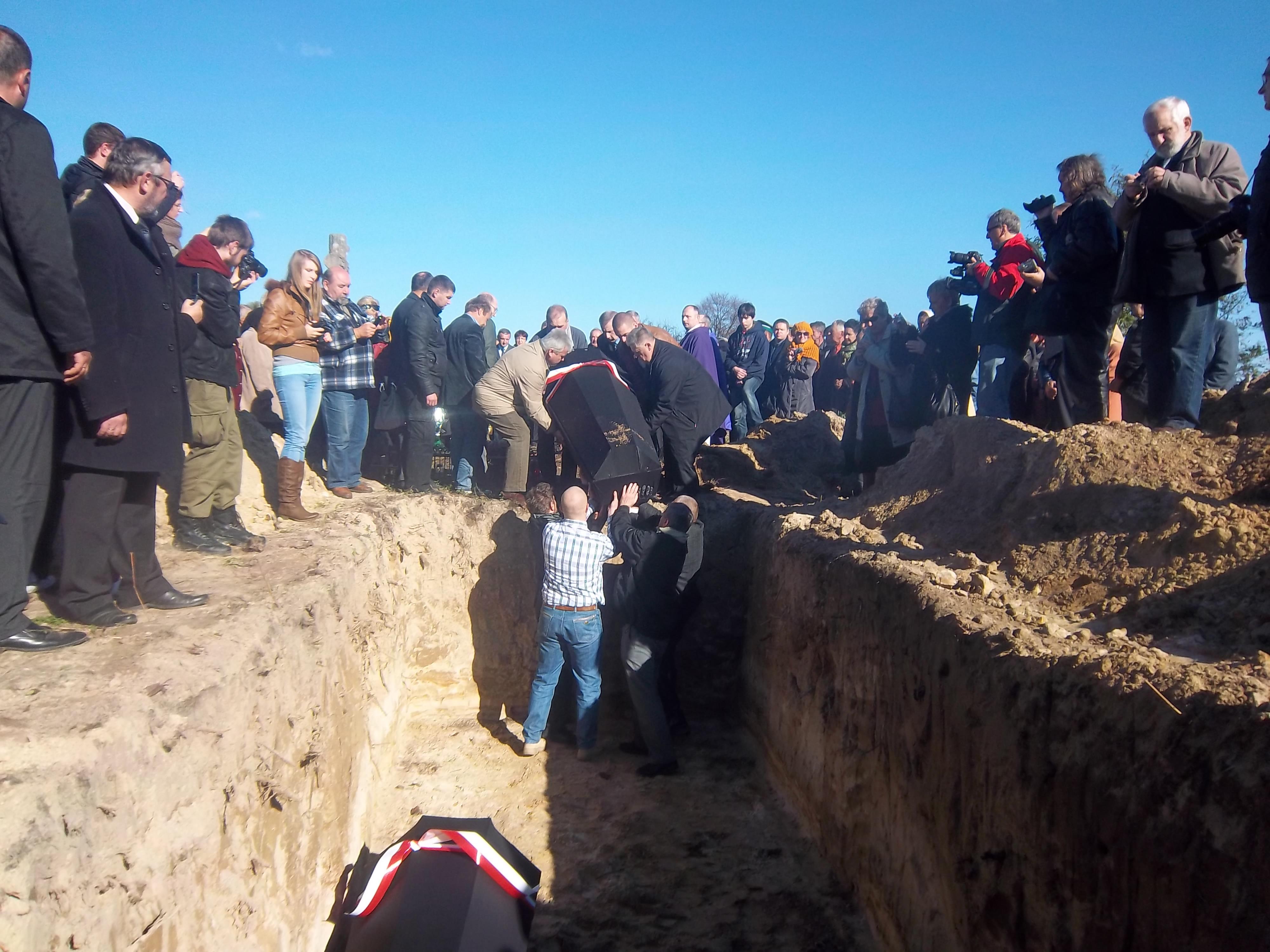 Останки укладывают в могилу