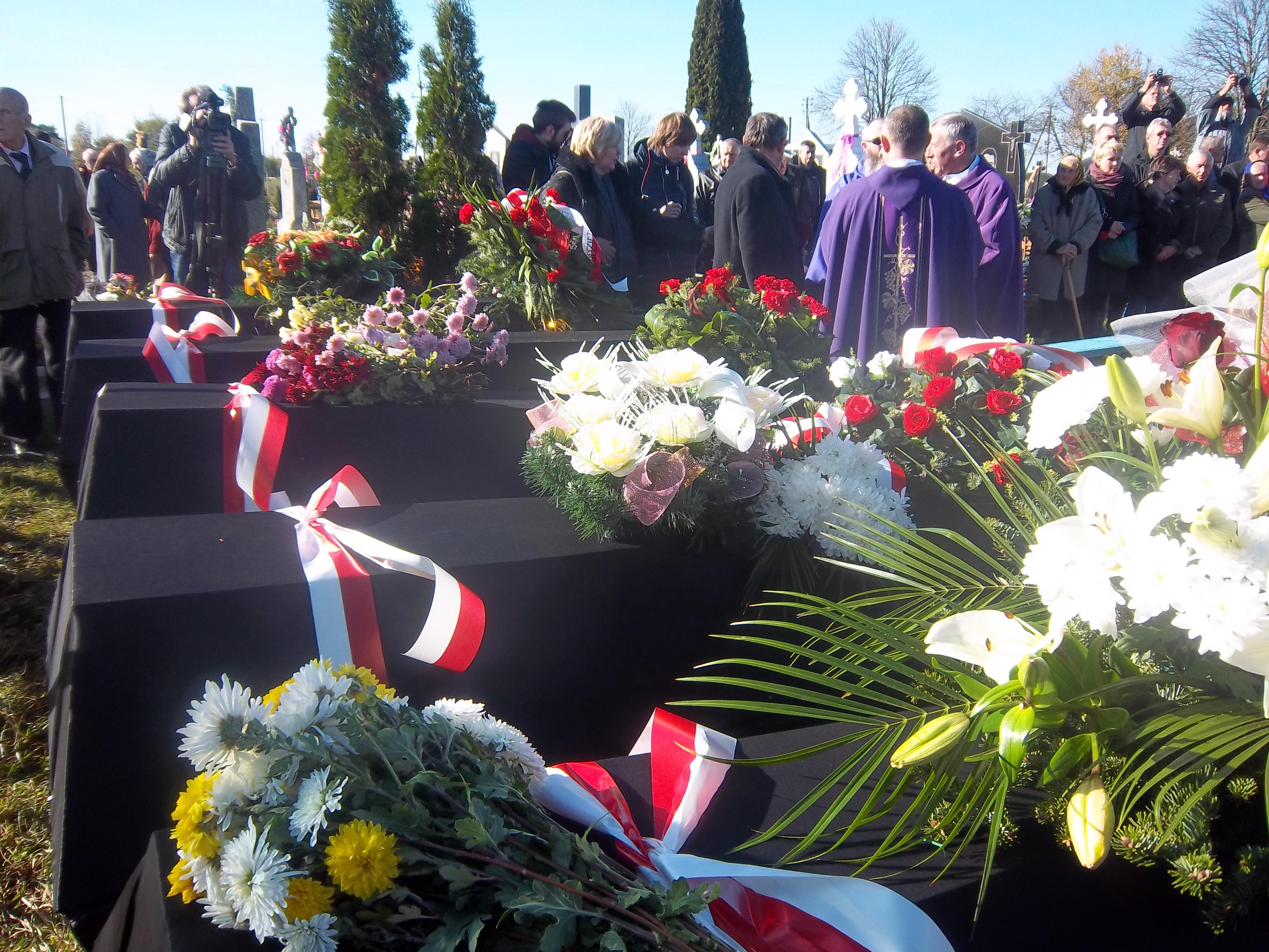 Гробы с останками опоясаны бело-красной лентой