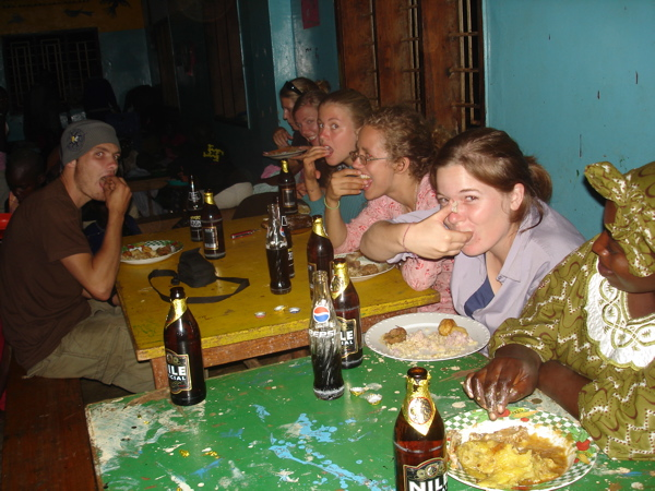 Ugandans eat with their hands. Demonstration: by all the muzungus