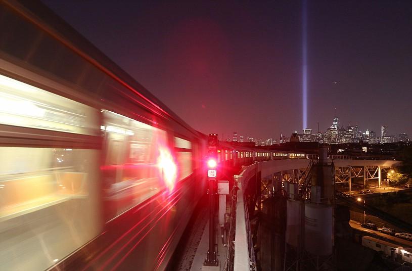Нью-Йорк. Свет светит вверх на Манхэттене, когда состав  метро проходит Brooklyn
