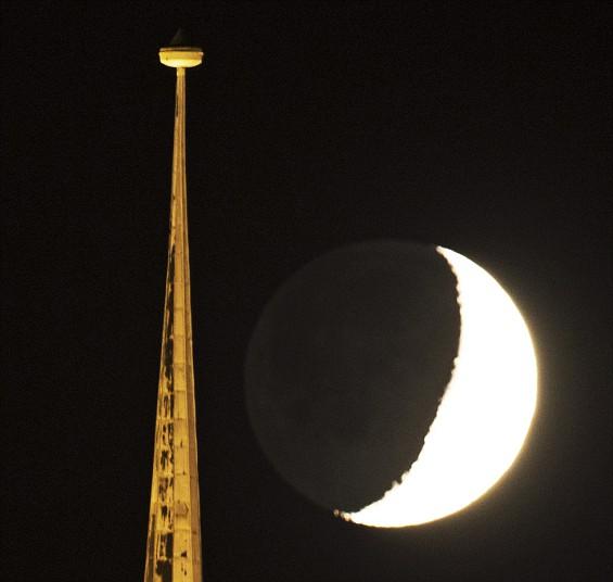 Убывающая луна поднимается за вершины на церковь Святой Севери в Эрфурте, Германия
