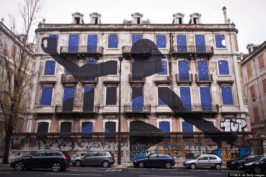 A giant man is sticking out his head and arms of the windows of an old abandoned building. The art piece is made by street artist Sam3 who is one out of 16 artists who took part in the Crono Project in Lisbon. Portugal 2013.