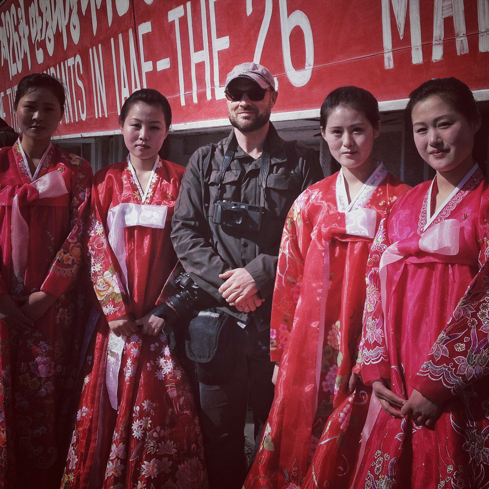 taken with Guttenfelder's iPhone by AP reporter Eric Talmadge. David Guttenfelder poses for a photo with North Korean women in traditional dresses before the start of a marathon at Kim Il Sung Stadium in Pyongyang, North Korea.