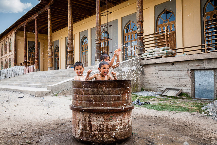 Tajik children playing in drum of water outside mosque