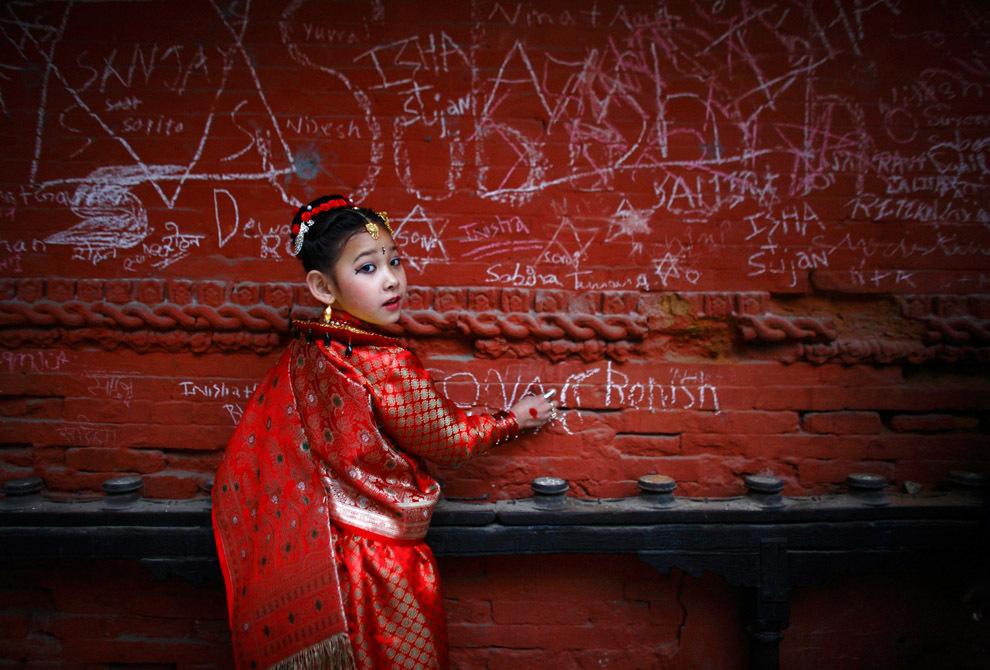 Семилетняя девочка пишет на стене храма Сарасвати на фестивале Васант-панчами в Катманду