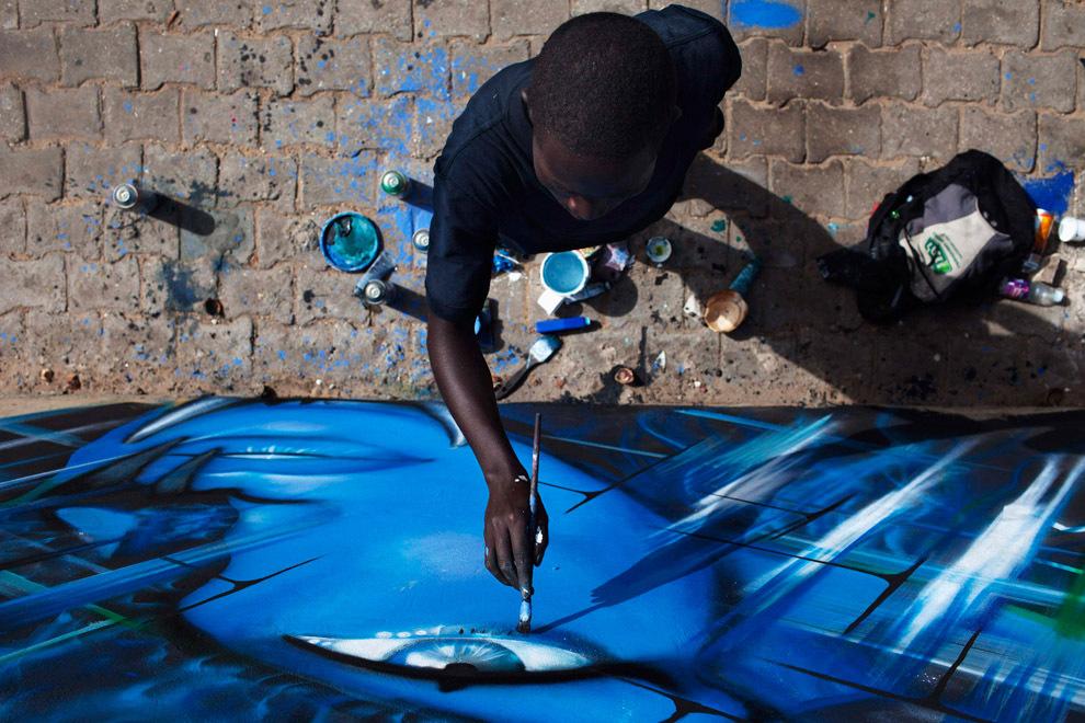Художник рисует граффити возле шоссе в Дакаре Сенегал 9 мая 2013 года