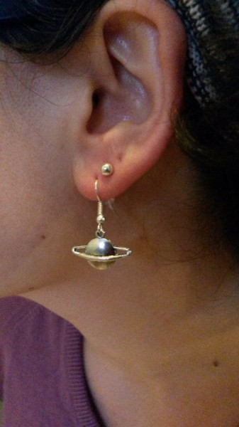 My ear wearing a silver earring in the shale of a planet with a ring around it
