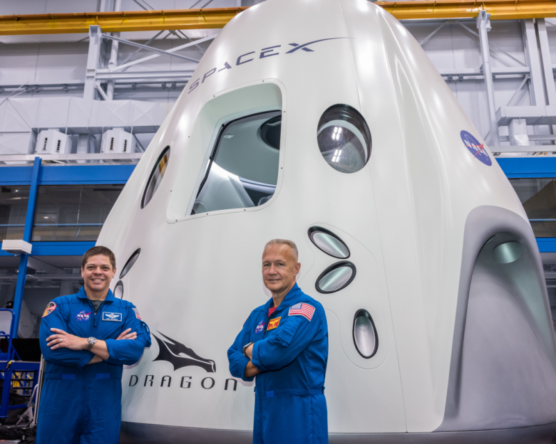 NASA's Bob Behnken and Doug Hurley pictured in front of a SpaceX Crew Dragon