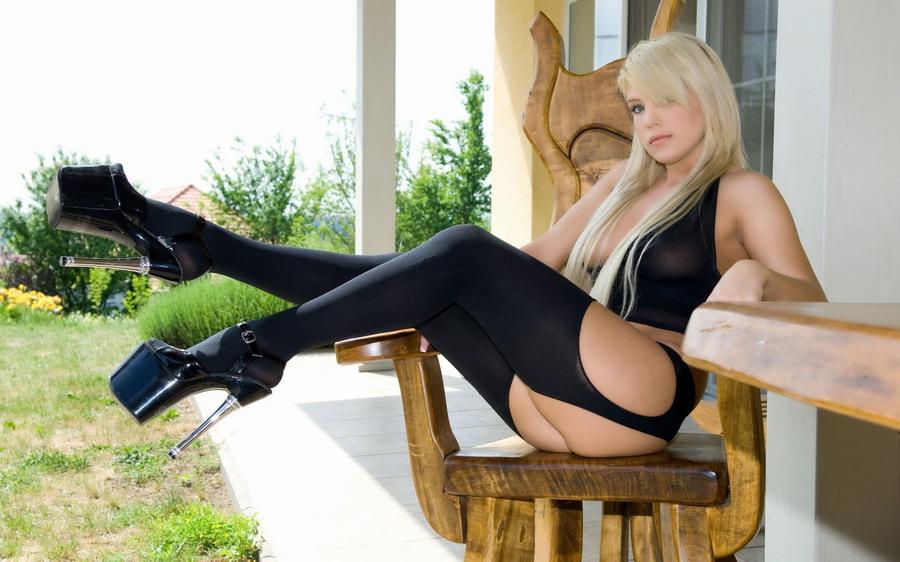 Девушка в черных чулках на высоких каблуках сидит на деревянном стуле возле
