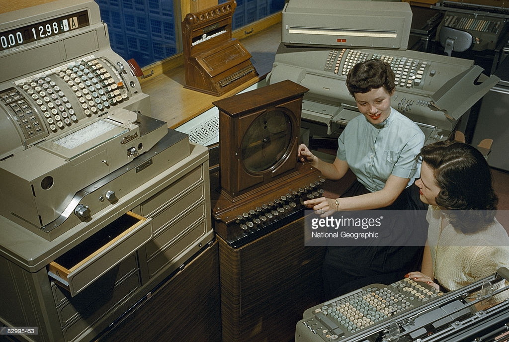 1955 Women sit amid varied machines made by National Cash Register Company, Dayton, Ohio by B. Anthony Stewart.jpg