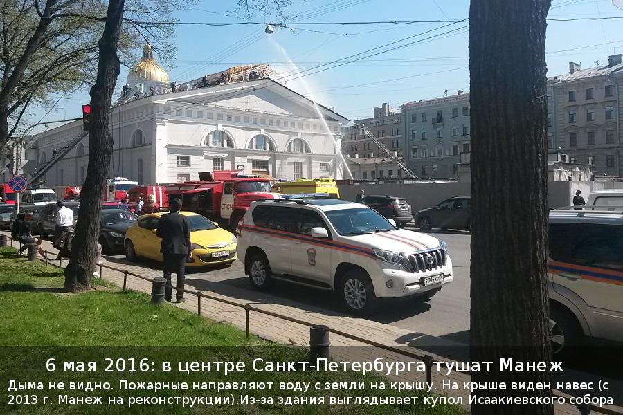 Дыма не видно. Пожарные направляют воду с земли на крышу. На крыше виден навес (с 2013 г. Манеж на реконструкции). Из-за здания выглядывает купол Исаакиевского собора
