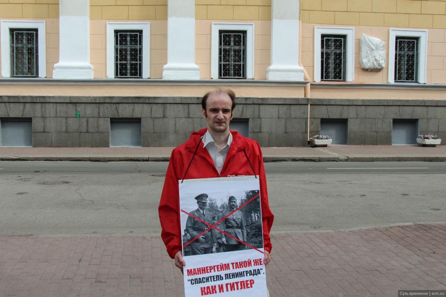 Активист «Сути времени» с протестным плакатом перед доской о Маннергейме утром 16 июня