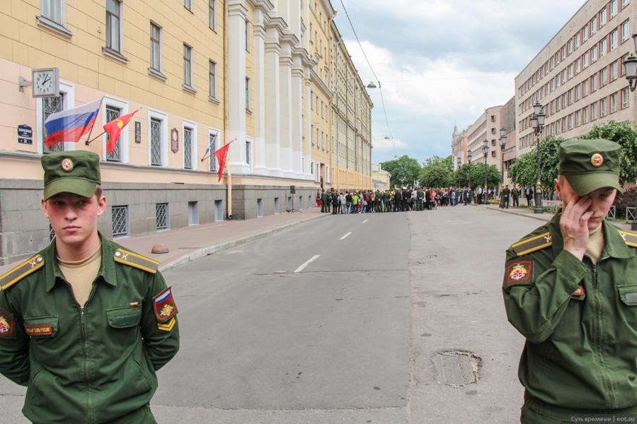 Вид на приведённую толпу с 50 метров из-за оцепления, в котором стоят курсанты 2-го года обучения. На левом нагрудном кармане нет лычек с фамилиями