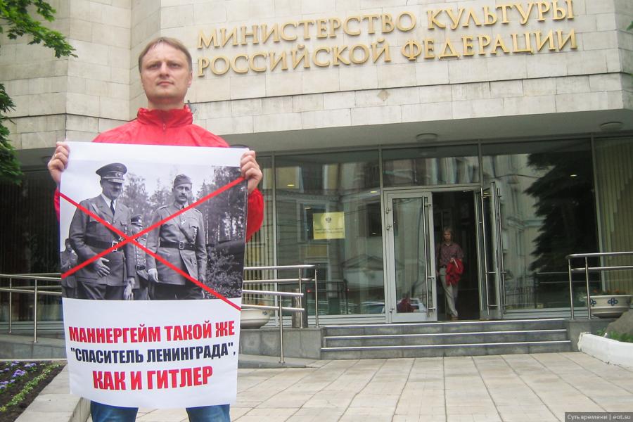 Активист «Сути времени» перед входом в Министерство культуры в Москве с плакатом «Маннергейм такой же 'спаситель Ленинграда', как и Гитлер»